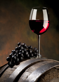 glass of red wine on a barrel